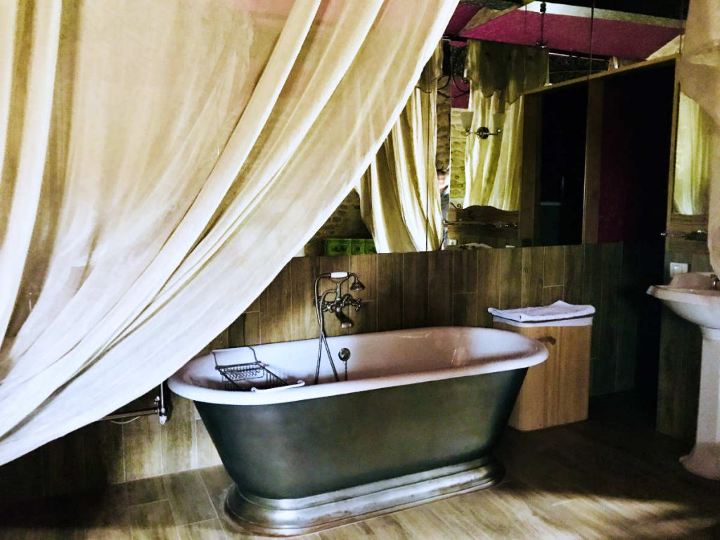 Bathroom in a French château separated from the bed by a curtain