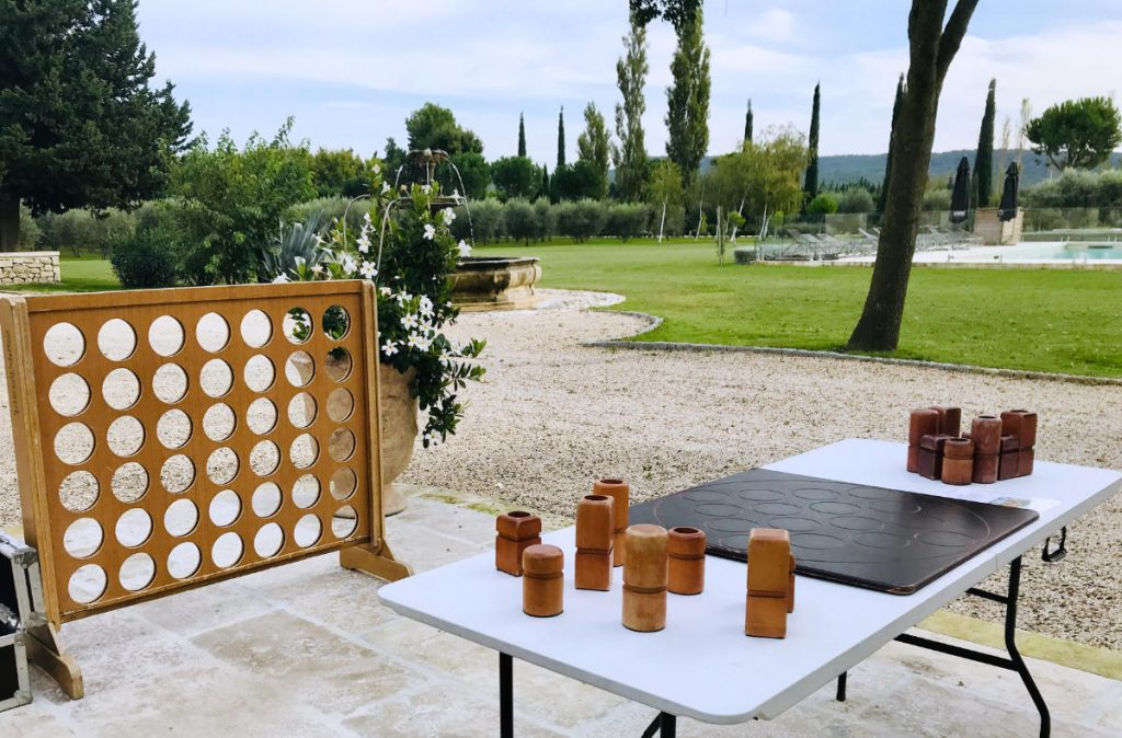 wooden game of connect 4 with swimming pool in background