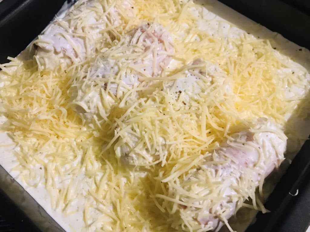 Quenelles covered in cream and cheese before being placed in the oven.