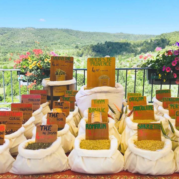 row of spices on a table at an outdoor farmers market, overlooking a valley in Provence - staples for a French pantry