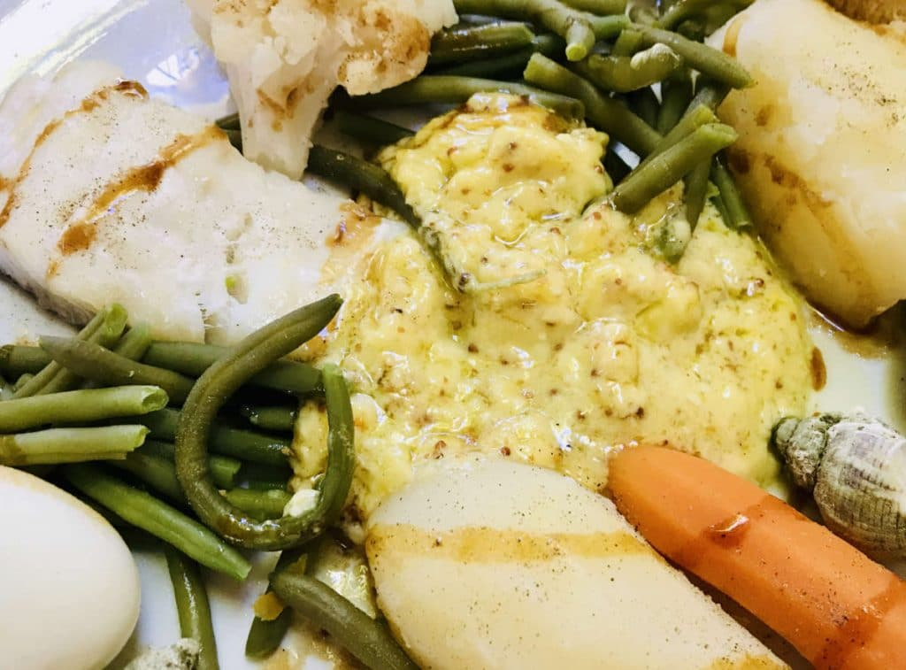 close up of aioli sauce on a plate with steamed fish, beans and carrots