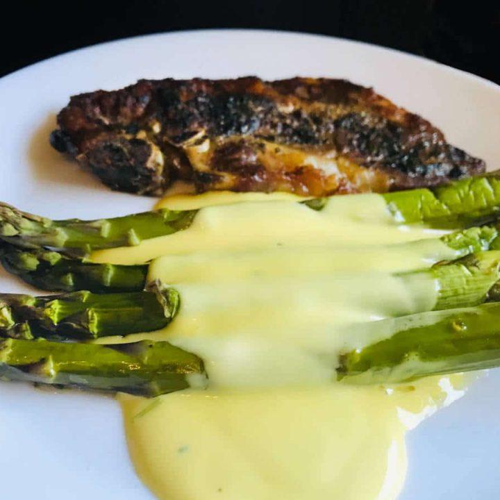 hollandaise sauce on asparagus, with a side of pork