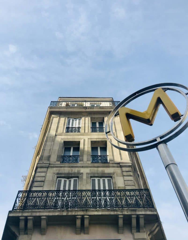 Paris metro sign in front of Hausmannian building